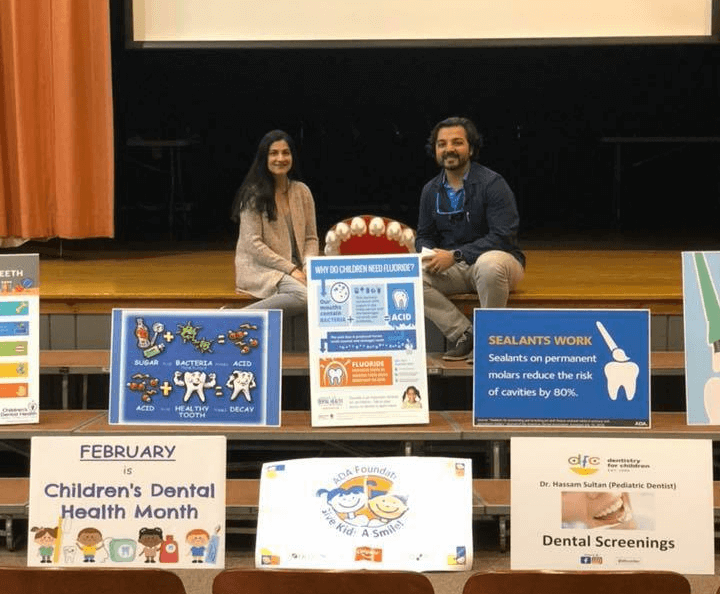 Dr. Shah & Dr. Sultan on a stage with signs